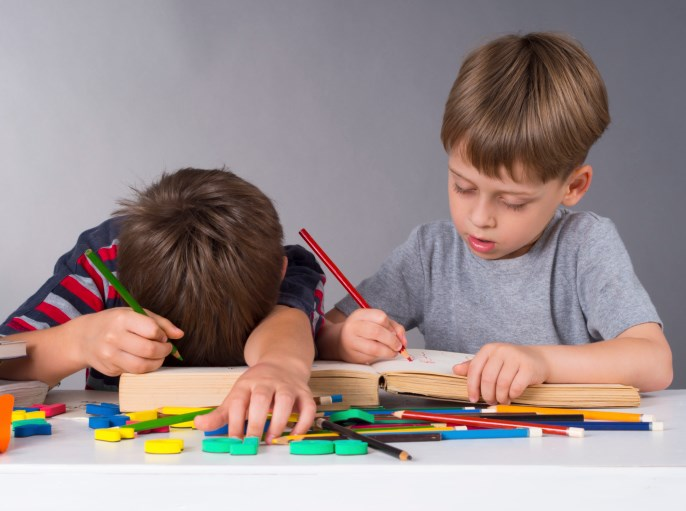 boy focused on coloring next to boy bored with head on table